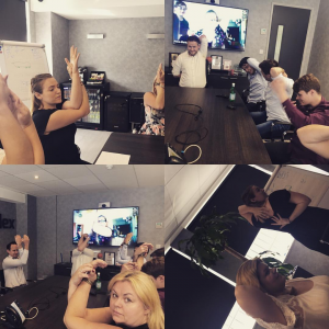 Four images of a Solis Yoga corporate class. People seated around a wooden office desk.